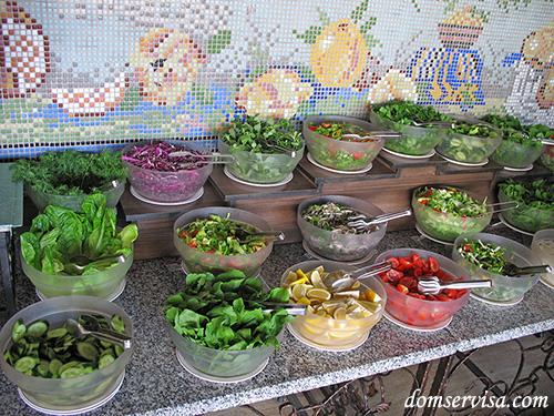 Второй стол с зеленью и нарезанными овощами, лимонами
